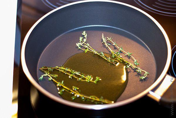 Разогреваем в сковородке масло и веточки пряных трав